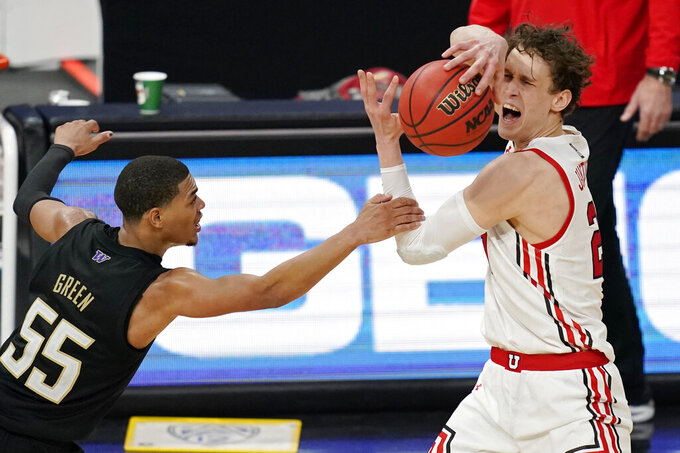 Washington's Quade Green (55) fouls Utah's Mikael Jantunen (20) during the second half of an NCAA college basketball game in the first round of the Pac-12 men's tournament Wednesday, March 10, 2021, in Las Vegas. (AP Photo/John Locher)