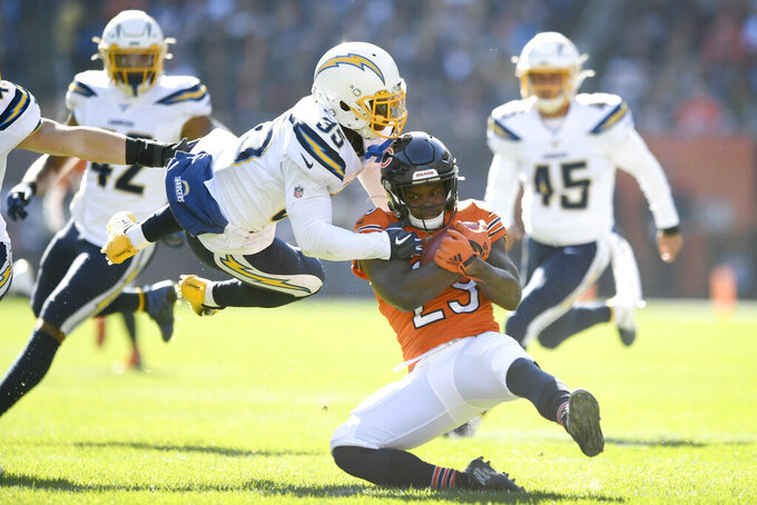 Chicago Bears running back Tarik Cohen is tackled by Los Angeles Chargers' Troymaine Pope (35) during the first half of an NFL football game, Sunday, Oct. 27, 2019, in Chicago. (AP Photo/Paul Beaty)