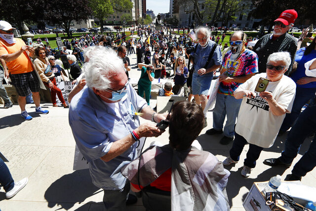 Barber Karl Manke, of Owosso, gives a free haircut on the steps of the State Capitol during a rally in Lansing, Mich., Wednesday, May 20, 2020. Barbers and hair stylists are protesting the state's stay-at-home orders, a defiant demonstration that reflects how salons have become a symbol for small businesses that are eager to reopen two months after the COVID-19 pandemic began. (AP Photo/Paul Sancya)