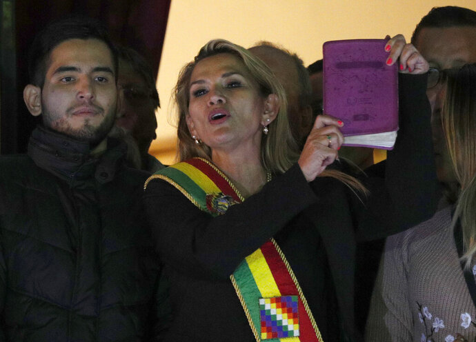FILE - In this Nov. 12, 2019 file photo, Bolivia's second Senate Vice President and opposition politician Jeanine Anez, center, wearing the Presidential sash and holding a Bible, addresses the crowd from the balcony of the Quemado palace after she declared herself interim president of the country, in La Paz, Bolivia. Anez announced on Thursday, Sept. 17, 2020, that she no longer will be a candidate in the upcoming presidential elections. (AP Photo/Juan Karita, File)