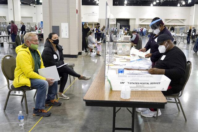 ARCHIVO - Empleados electorales, a la derecha, verifican las papeletas mientras observadores, a la izquierda, vigilan el recuento manual de los votos presidenciales en Wisconsin el viernes 20 de noviembre de 2020, en un centro de conteo en Milwaukee. (AP Foto/Nam Y. Huh)