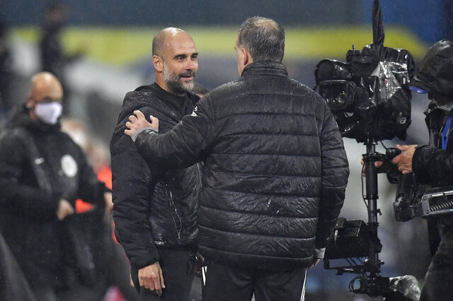 Manchester City's head coach Pep Guardiola, left, talks with Leeds United's head coach Marcelo Bielsa at the end of the English Premier League soccer match between Leeds United and Manchester City at Elland Road in Leeds, England, Saturday, Oct. 3, 2020. (Paul Ellis/Pool via AP)
