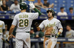 Oakland Athletics' Ramon Laureano (22) celebrates his grand slam off Tampa Bay Rays pitcher Colin Poche with Matt Olson (28) during the eighth inning of a baseball game Wednesday, June 12, 2019, in St. Petersburg, Fla. (AP Photo/Chris O'Meara)