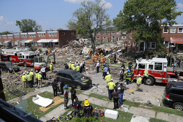 Rescue officials work near the rubble in the aftermath of an explosion in Baltimore, Monday, Aug. 10, 2020. Baltimore firefighters say an explosion has leveled several homes in the city. (AP Photo/Julio Cortez)