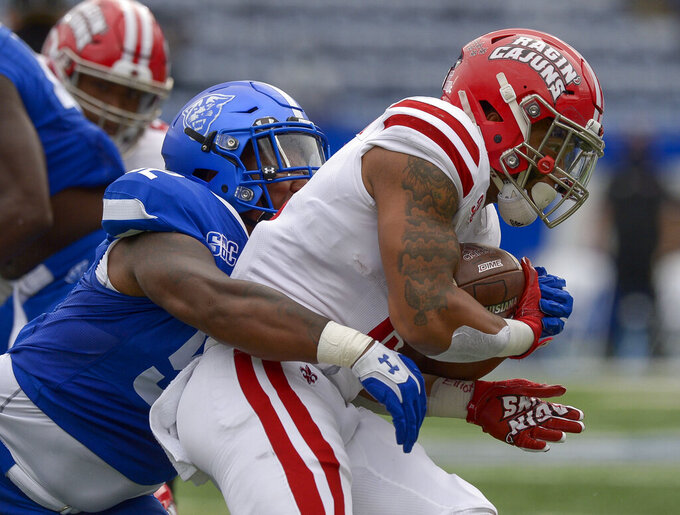 Georgia State nose guard Dontae Wilson (52) makes a tackle on Louisiana-Lafayette running back Elijah Mitchell (15) in the first half of an NCAA college football game, Saturday, Sept. 19, 2020, in Atlanta. (Daniel Varnado/Atlanta Journal-Constitution via AP)