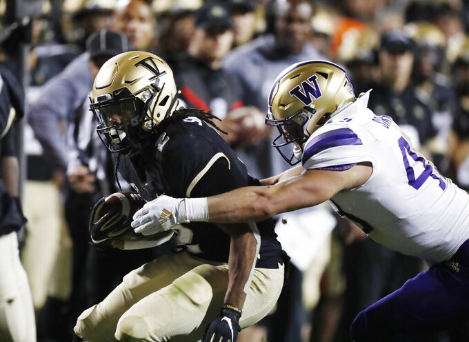 Colorado wide receiver Laviska Shenault Jr., left, is tackled, after a short gain, by Washington linebacker Jackson Sirmon during the first half of an NCAA college football game Saturday, Nov. 23, 2019, in Boulder, Colo. (AP Photo/David Zalubowski)