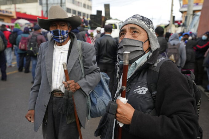 Men stand on the Inter American Highway as part of a crowd blocking it during a nationwide strike in Totonicapan, Guatemala, early Thursday, July 29, 2021. People are calling for the resignation of Guatemalan President Alejandro Giammattei and Attorney General Consuelo Porras after they fired Special Prosecutor Against Impunity Juan Francisco Sandoval. (AP Photo/Moises Castillo)