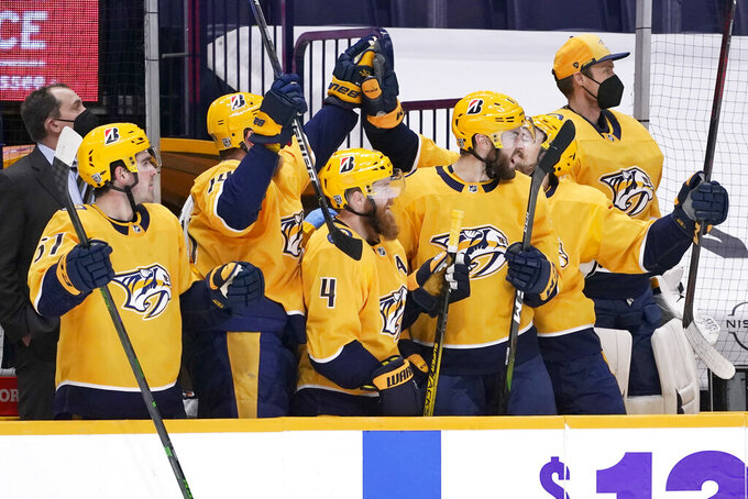 Nashville Predators players celebrate on the bench after a goal against the Columbus Blue Jackets in the third period of an NHL hockey game Sunday, Feb. 28, 2021, in Nashville, Tenn. (AP Photo/Mark Humphrey)