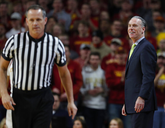 TCU head coach Jamie Dixon, right, smiles back at an official after he was charged with a technical foul during the first half of an NCAA college basketball game against Iowa State, Saturday, Feb. 9, 2019, in Ames. (AP Photo/Matthew Putney)