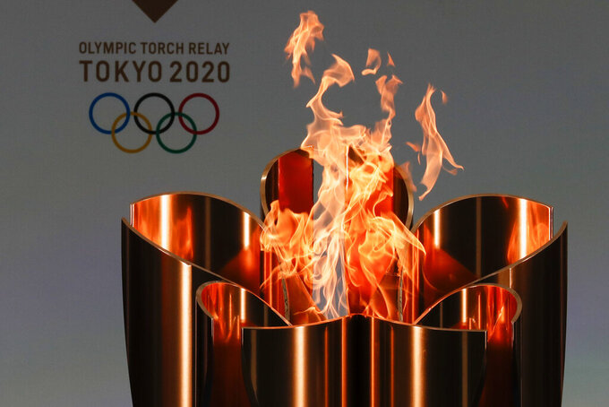 """FILE - In this March 25, 2021, file photo, the celebration cauldron is seen lit on the first day of the Tokyo 2020 Olympic torch relay in Naraha, Fukushima prefecture, northeastern Japan. Tokyo pitched itself as """"a safe pair of hands"""" when it was awarded the Olympics 7 1/2 years ago. Now, nothing is certain as Tokyo's postponed Olympics hit the 100-days-to-go mark on Wednesday, April 14, 2021. (Kim Kyung-Hoon/Pool Photo via AP, File)"""