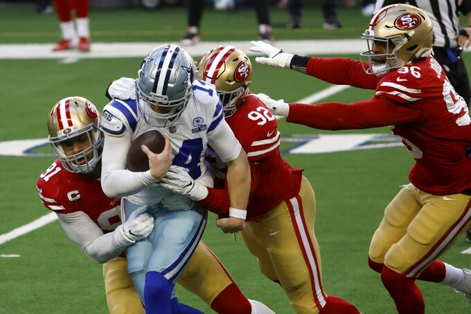 San Francisco 49ers' Arik Armstead (91) and Kerry Hyder Jr. (92) wrap up and sack Dallas Cowboys quarterback Andy Dalton (14) with help from defensive end Dion Jordan (96) in the first half of an NFL football game in Arlington, Texas, Sunday, Dec. 20, 2020. (AP Photo/Ron Jenkins)