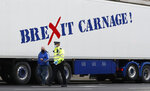 A policeman escorts the driver of a shellfish export truck as he is stopped for an unnecessary journey in London, Monday, Jan. 18, 2021, during a demonstration by British Shellfish exporters to protest Brexit-related red tape they claim is suffocating their business. The drivers were later stopped by police and issued with fines for an 'unnecessary journey' due to the national lockdown to curb the spread of the coronavirus. (AP Photo/Alastair Grant)