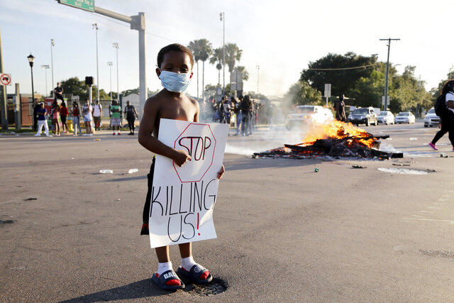 Five-year-old Michael Veteri stands at an intersection where the road remained closed during a protest Sunday, May 31, 2020, in Tampa Fla., over the death of George Floyd. Floyd died May 25 after he was pinned at the neck by a Minneapolis police officer. (Douglas R. Clifford/Tampa Bay Times via AP)