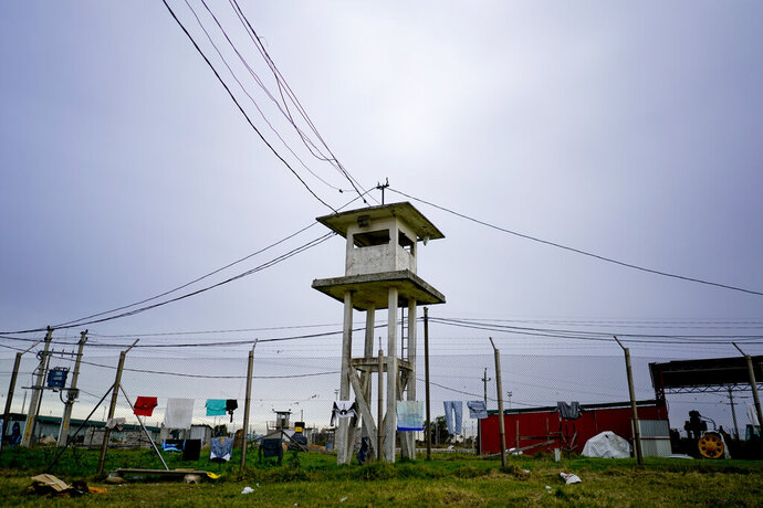 In this May 29, 2019 photo, an abandoned guard tower stands in the inner court area as clothes hang from a fence of the Punta de Rieles prison in Montevideo, Uruguay. Punta de Rieles is an exception not only in Uruguay but in Latin America where penitentiary systems are synonymous with inhumane treatment, inhospitable conditions and very high recidivism rates. (AP Photo/Matilde Campodonico)