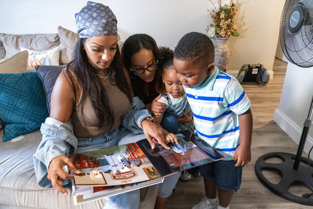 Siblings, from left, Katherine, Jennifer, Jazzmyn and Zavion look at their mother Lunisol Guzman's wedding album, Thursday, Sept. 17, 2020, in Newark, N.J. Four-year-old Zavion and 2-year-old Jazzmyn have been taken in by the oldest of Lunisol Guzman's other three children, Katherine and Jennifer, after she died from symptoms of coronavirus. Lunisol Guzman had adopted them when she was in her 40s. (AP Photo/Mary Altaffer)
