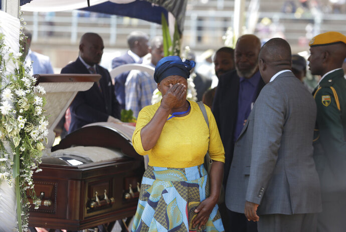 A mourner weeps after viewing the coffin with former Zimbabwean President Robert Mugabe at the Rufaro Stadium in Harare, Friday, Sept. 13, 2019, where the body is on view at the stadium for a second day. Mugabe died last week in Singapore at the age of 95. He led the southern African nation for 37 years before being forced to resign in late 2017. (AP Photo/Themba Hadebe)