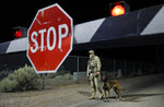 A security guard stands at an entrance to the Nevada Test and Training Range near Area 51 Friday, Sept. 20, 2019, near Rachel, Nev. People gathered at the gate inspired by the