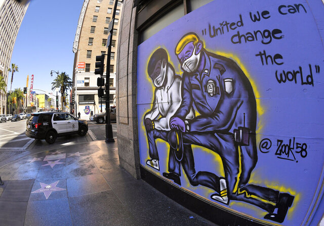 A mural is seen on a boarded up business as a Los Angeles Police Department car drives by, Tuesday, June 9, 2020, in the Hollywood section of Los Angeles. Many businesses were boarded up during protests over the death of George Floyd. Floyd, a black man died after being restrained by Minneapolis police officers on May 25. (AP Photo/Mark J. Terrill)