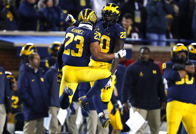 Michigan defensive back's Tyree Kinnel (23) and Brad Hawkins (20) celebrate after a play in the second half of an NCAA college football game against Indiana in Ann Arbor, Mich., Saturday, Nov. 17, 2018. Michigan won 31-20. (AP Photo/Paul Sancya)