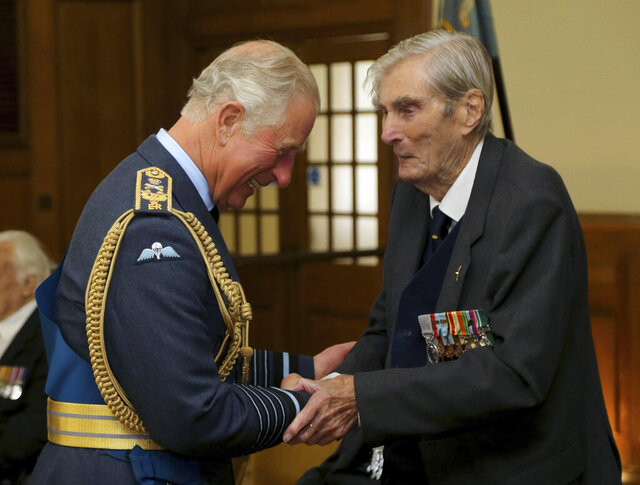 FILE - In this Sept. 17, 2017 file photo, Britain's Prince Charles, left, shakes hands with Battle of Britain veteran Wing Commander Paul Farnes, in Dover, England. One of the last remaining and most decorated Battle of Britain fighter pilots who helped protect Britain during World War II has died. The Battle of Britain Memorial Trust said Wing Commander Paul Farnes died at his home Tuesday, Jan. 28, 2020 at the age of 101. (Gareth Fuller/PA via AP, File)
