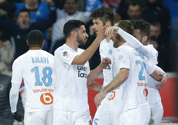 Marseille's players celebrate after scoring their side's first goal during the French League One soccer match between Lille and Marseille at the Lille Metropole stadium in Villeneuve d'Ascq, northern France, Sunday, Feb. 16, 2020. (AP Photo/Michel Spingler)