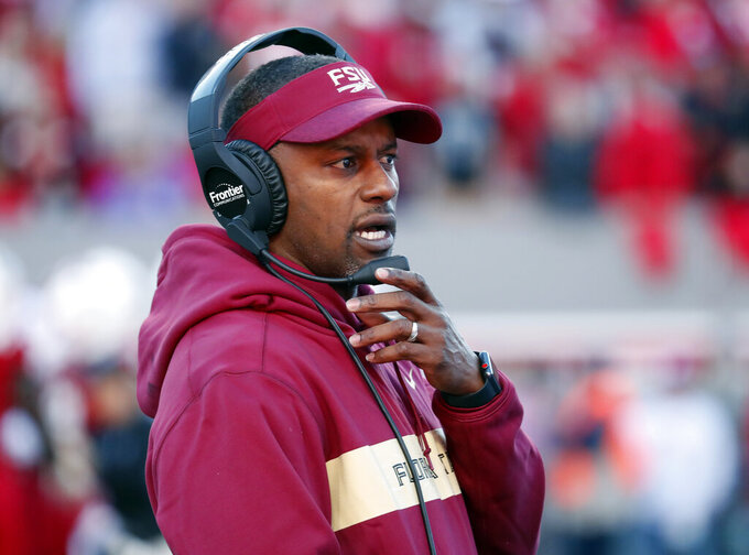 FILE - In this Saturday, Nov. 3, 2018 file photo, Florida State head coach Willie Taggart confers on his headset during the first half of an NCAA college football game against North Carolina State in Raleigh, N.C. Florida State and Miami were hoping signing day could help put to the negativity of 2018 to rest and provide a push toward better times. Coming off a 5-7 record in their first season under coach Willie Taggart, the Seminoles landed a top 20 class but struck out on a much-needed quarterback Wednesday, Feb. 6, 2019. (AP Photo/Chris Seward, File)