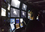 In this 2015 photo provided by the Monterrey Bay Aquarium Research Institute, Kakani Katija works in the remote operated vehicle control room on MBARI's research vessel Western Flyer as the DeepPIV system illuminates a giant larvacean. The mucus structure the creature builds include two heart-like chambers that act as a maze for the food that drifts in, except there's only one way for them to go: into the larvacean's mouth. (Kim Reisenbichler/MBARI via AP)