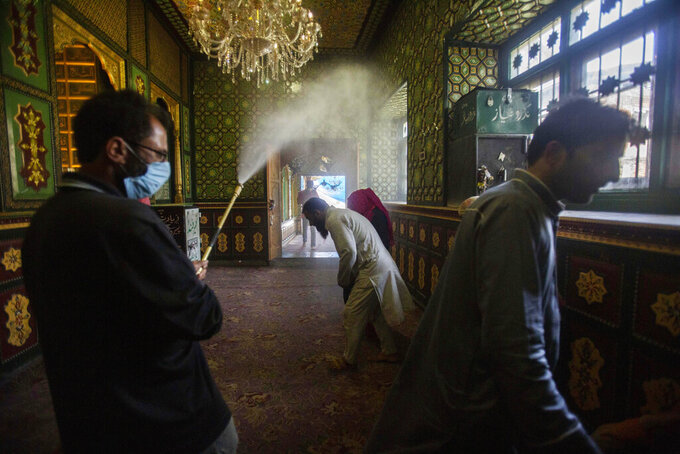 A Kashmiri municipal worker sprays disinfectants as a precautionary measure against coronavirus as a devotee ducks to avoid it inside a Muslim shrine in Srinagar, Indian controlled Kashmir, Sunday, Aug. 16, 2020. Shrines and other religious places across the Jammu and Kashmir reopened for devotees on Sunday after remaining closed for almost five months due to the COVID-19 outbreak. (AP Photo/Mukhtar Khan)