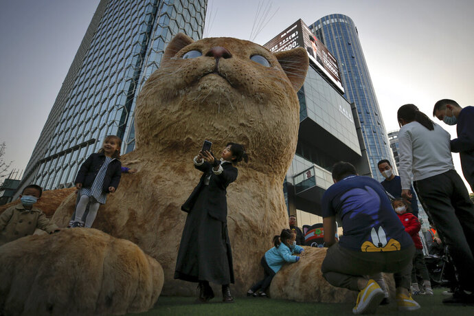 A woman takes a selfie as visitors wearing face masks to help curb the spread of the coronavirus gather near a giant cat structure on display at a commercial office building in Beijing, Sunday, Oct. 18, 2020. (AP Photo/Andy Wong)