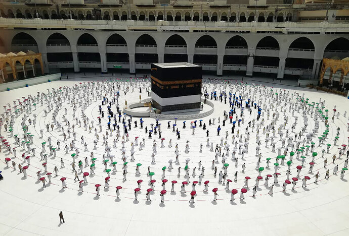 Hundreds of Muslim pilgrims circle the Kaaba, the cube-shaped structure in the Grand Mosque, as they observe social distancing to protect themselves against the coronavirus, in the Muslim holy city of Mecca, Saudi Arabia, Wednesday, July 29, 2020 During the first rites of hajj, Muslims circle the Kaaba counter-clockwise seven times while reciting supplications to God, then walk between two hills where Ibrahim's wife, Hagar, is believed to have run as she searched for water for her dying son before God brought forth a well that runs to this day. (AP Photo)