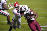 Georgia defensive back Lewis Cine (16) tackles South Carolina running back Kevin Harris (20) during the first half of an NCAA college football game Saturday, Nov. 28, 2020, in Columbia, S.C. (AP Photo/Sean Rayford)