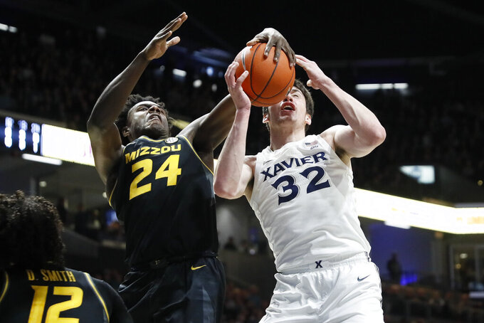 Missouri's Kobe Brown (24) blocks a shot by Xavier's Zach Freemantle (32) during the first half of an NCAA college basketball game Tuesday, Nov. 12, 2019, in Cincinnati. (AP Photo/John Minchillo)