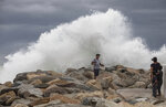 A tourist poses for a photo in front breaking waves before the expected arrival of Hurricane Lorena, in Los Cabos, Mexico, Friday, Sept. 20, 2019. Hurricane Lorena neared Mexico's resort-studded Los Cabos area Friday as owners pulled their boats from the water, tourists hunkered down in hotels, and police and soldiers went through low-lying, low-income neighborhoods urging people to evacuate. (AP Photo/Fernando Castillo)