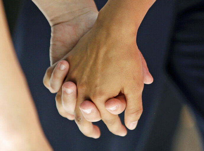 "FILE - In this Wednesday, July 15, 2015 file photo, a lesbian couple holds hands in Salt Lake City. Released on Thursday, Aug. 29, 2019, the largest study of its kind found new evidence that genes contribute to same-sex sexual behavior, echoing research that says there is no single ""gay gene."" (AP Photo/Rick Bowmer)"