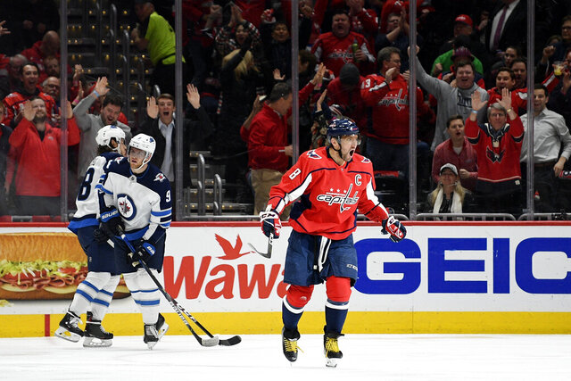 Washington Capitals left wing Alex Ovechkin (8), of Russia, celebrates his goal, next to Winnipeg Jets defenseman Nathan Beaulieu (88) and center Andrew Copp (9) during the first period of an NHL hockey game Tuesday, Feb. 25, 2020, in Washington. (AP Photo/Nick Wass)