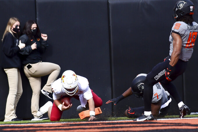 Iowa State quarterback Brock Purdy (15) scores a touchdown against Oklahoma State after evading Oklahoma State defenders Amen Ogbongbemiga (7) and Sean Michael Flanagan (18) during an NCAA college football game Saturday, Oct. 24, 2020, in Stillwater, Okla. (AP Photo/Brody Schmidt)