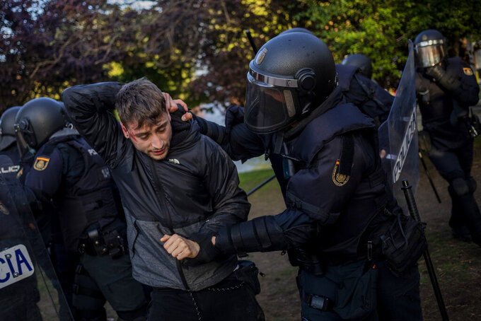 Spanish police detain a left-wing protester in Madrid's Vallecas neighborhood, Spain, Wednesday, April 7, 2021. Spanish police have used batons to keep protesters away from a campaign event of the far-right Vox party in Madrid. Scuffles started Wednesday when Santiago Abascal, the national leader of Vox, approached a crowd gathered to protest the party rally in Madrid's Vallecas neighborhood, a traditional left-wing bastion. Riot peace charged the bunches of protesters to keep them away from the party campaign event for upcoming regional elections. (AP Photo/Bernat Armangue)