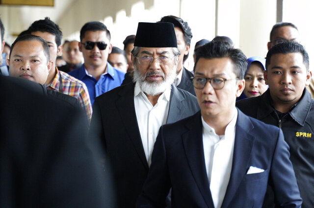 FILE- In this Monday, Nov. 5, 2018, file photo, former chief minister of Saba state on Borneo island, Musa Aman, center, arrives at the High Court in Kuala Lumpur, Malaysia. Musa Aman was among several senior politicians from the United Malays National Organization who were charged with corruption after the party's shocking defeat in 2018 polls. The party became part of a new alliance government under Prime Minister Muhyiddin Yassin that came into power in March. (AP Photo/Yam G-Jun, File)