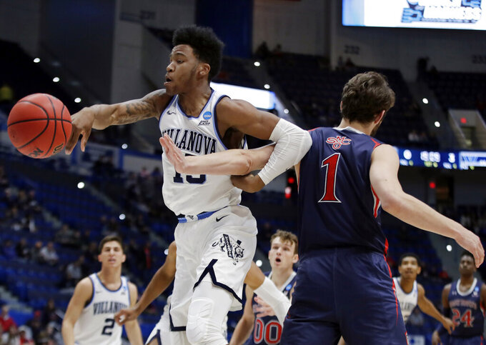 Villanova's Saddiq Bey (15) and St. Mary's Jordan Hunter (1) become entangled as they go for the ball during the first half of a first round men's college basketball game in the NCAA Tournament, Thursday, March 21, 2019, in Hartford, Conn. (AP Photo/Elise Amendola)
