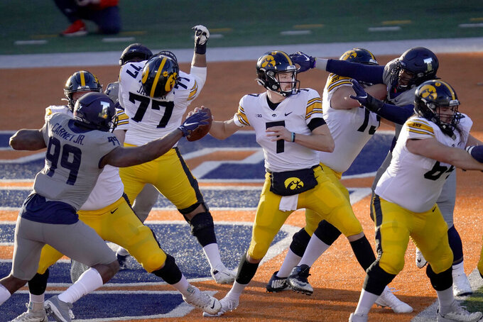 Iowa quarterback Spencer Petras is pressured by Illinois defensive lineman Owen Carney Jr. (99) and Roderick Perry II during the first half of an NCAA college football game Saturday, Dec. 5, 2020, in Champaign, Ill. (AP Photo/Charles Rex Arbogast)