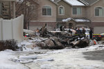 Firefighters and other investigators look at the debris from a small private plane that crashed in a residential area Wednesday, Jan. 15, 2020, in Roy, Utah. The small plane crashed Wednesday, killing the pilot as the aircraft narrowly avoided hitting any townhomes, authorities said. (Ben Dorger/Standard-Examiner via AP)