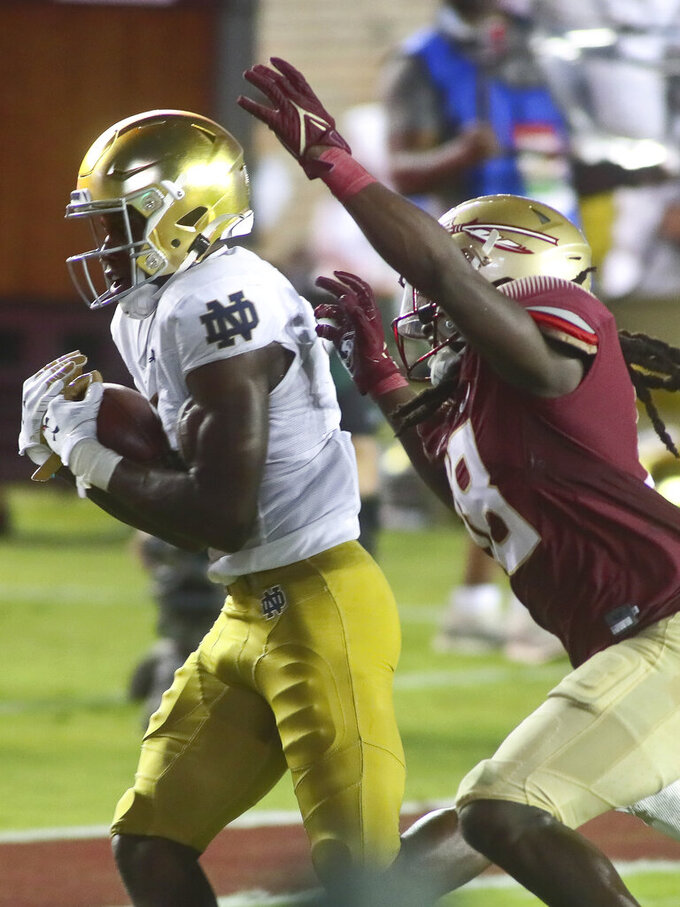 Notre Dame wide receiver Kevin Austin Jr. (4) heads for a touchdown after catching a pass as Florida State defensive back Travis Jay (18) reaches for him in the third quarter of an NCAA college football game Sunday, Sept. 5, 2021, in Tallahassee, Fla. (AP Photo/Phil Sears)
