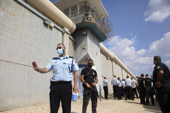 Police officers and prison guards inspect the scene of a prison escape outside the Gilboa prison in northern Israel, Monday, Sept. 6, 2021. Israeli forces on Monday launched a massive manhunt in northern Israel and the occupied West Bank after several Palestinian prisoners escaped overnight from the high-security facility in an extremely rare breakout. (AP Photo/Sebastian Scheiner)