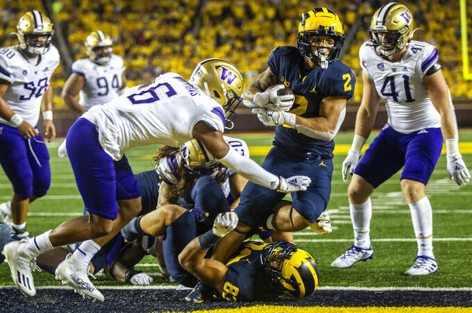 Michigan running back Blake Corum (2) steps over tight end Erick All (83) and past Washington defensive back Cameron Williams (6) to score a touchdown in the fourth quarter of an NCAA college football game in Ann Arbor, Mich., Saturday, Sept. 11, 2021. (AP Photo/Tony Ding)