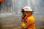 A firefighter covers his face while battling the Morton Fire near Bundanoon, New South Wales, Australia, on Thursday, Jan. 23, 2020. (AP Photo (AP Photo/Noah Berger)