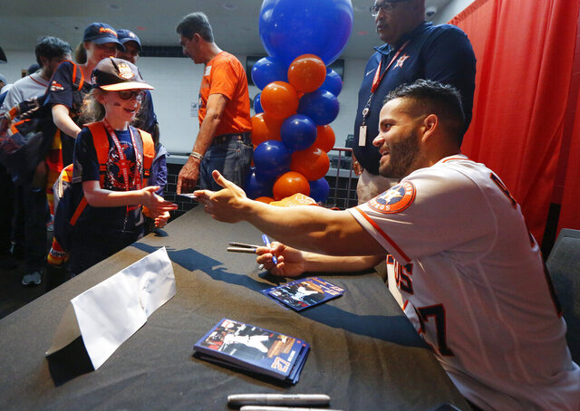 Jose Altuve signs autographs for young fans during the baseball team's FanFest at Minute Maid Park on Saturday, Jan. 18, 2020, in Houston. (Steve Gonzales/Houston Chronicle via AP)