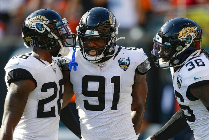 Jacksonville Jaguars defensive end Yannick Ngakoue (91) celebrates his interception and touchdown run in the second half of an NFL football game against the Cincinnati Bengals, Sunday, Oct. 20, 2019, in Cincinnati. (AP Photo/Gary Landers)