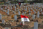 An Indonesian national Red-White flag flutters at the grave of a COVID-19 victim at Rorotan Cemetery in Jakarta, Indonesia, Wednesday, Sept. 1, 2021. In the graveyard on Jakarta's outskirts, portraits of the dead, bouquets of flowers and other mementos serve as reminders of the deadly coronavirus wave that battered Indonesia over the summer. (AP Photo/Achmad Ibrahim)