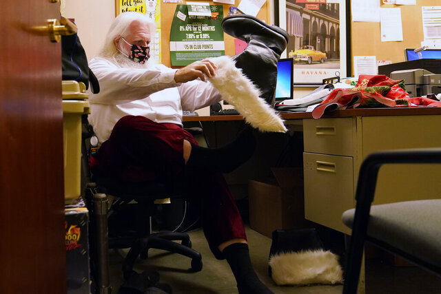 Brad Six wears a protective face mask as he puts on his boots preparing to work as Santa Claus at Bass Pro Shops, Friday, Nov. 20, 2020, in Miami. This is Santa Claus in the Coronavirus Age, where visits are done with layers of protection or moved online. Putting hundreds of kids a day onto your lap to talk directly into your face — that's not happening. (AP Photo/Lynne Sladky)