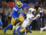 UCLA defensive back Kenny Churchwell III, bottom, tackles Colorado running back Jaren Mangham on a run attempt during the first half of an NCAA college football game as Odua Isibor looks on in Los Angeles, Saturday, Nov. 2, 2019. (AP Photo/Kelvin Kuo)